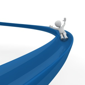 An anonymous figure sliding down a blue slide